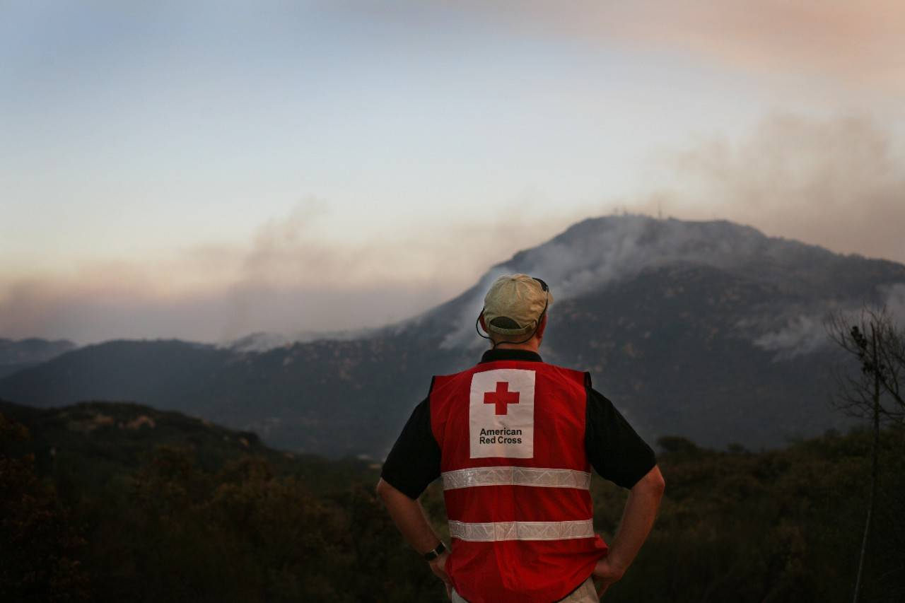 Red Cross worker Ken Krueger watches the Harris Fire burning in the southeastern section of San Diego County.