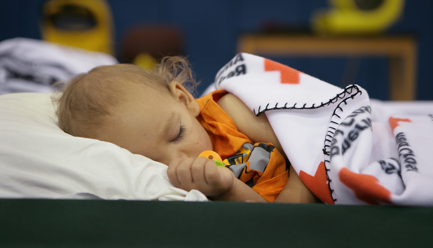 Child sleeps in a Red Cross shelter