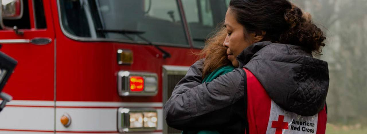 Volunteer hugs home fire victim