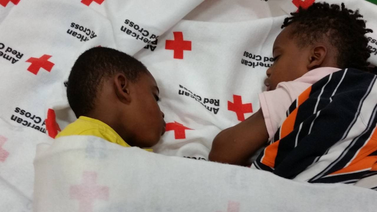 Young Chris and Frederick Moore and their family escape the chaos of the ongoing severe weather in Houston in an American Red Cross Respite Center near their home.