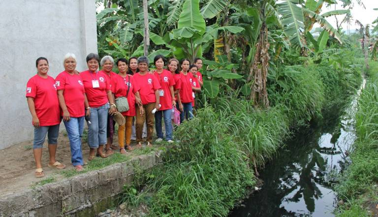 Philippine Red Cross volunteers stand near canal