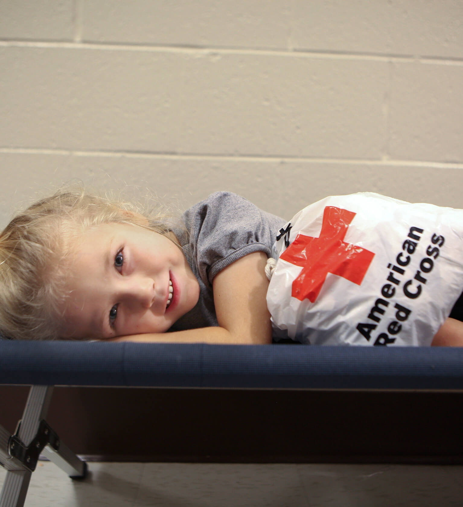 little girl on cot in shelter