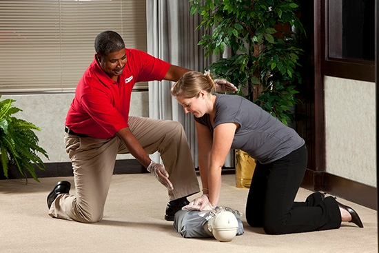 CPR instructor teaches student chest compressions