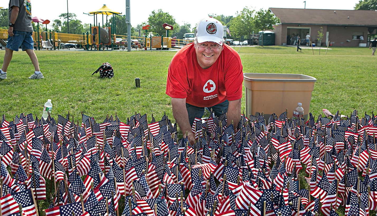 Red Cross Volunteer Plants Flags