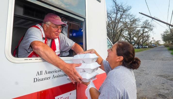 Hurricane survivor Jackie Fiorova receives hot meals for her family from Red Cross volunteer Russ Van Skike in Woodsboro, Texas. Jackie's home and neighborhood suffered sever damage.