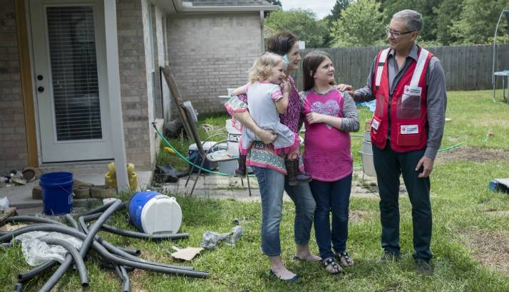 Amanda Garrison shows Marco Bracamontes of the American Red Cross some of her damaged possessions