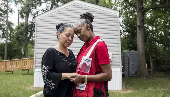 Cheryl Burton, a volunteer with the American Red Cross speaks with Maria Rutila Acevedo and Benito Flores whose house in Houston, TX was flooded by Hurricane Harvey.