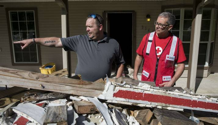Chris Strong shows Marco Bracamontes of the American Red Cross how his house was damaged by Hurricane Harvey, in Vidor, TX.