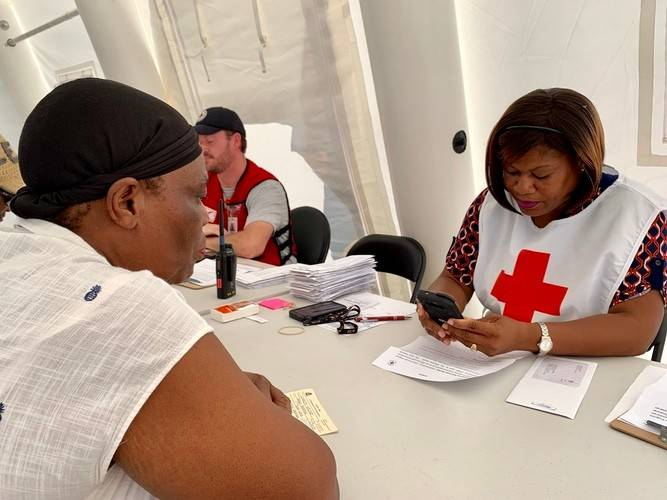 Bahamas Red Cross volunteer Pamela helps her neighbor to obtain aid