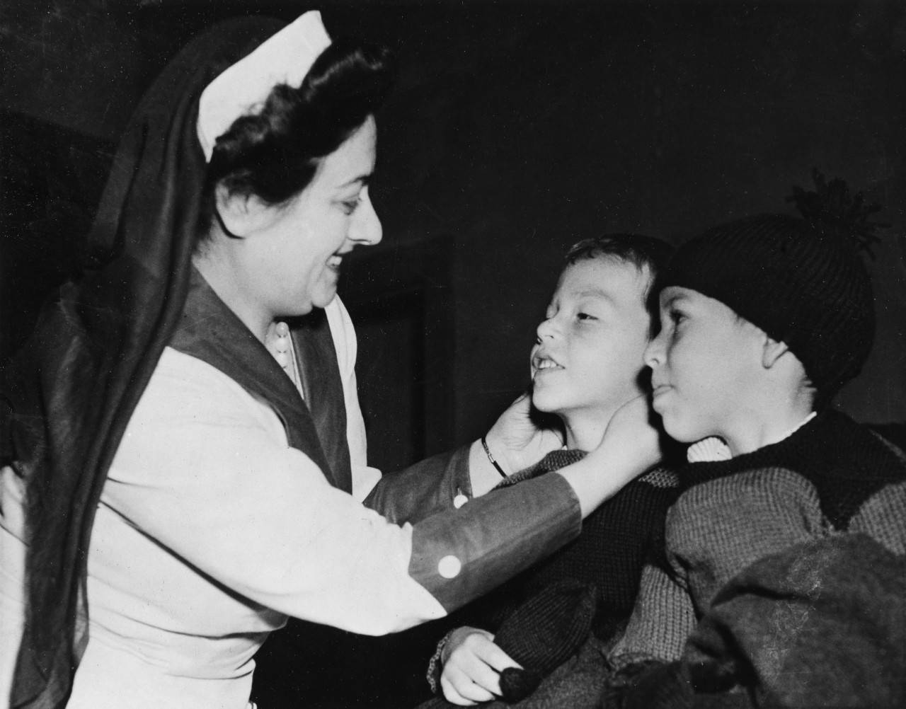 January 1942. Thomas Carroll Jr., 5, and his brother, Jimmy, were evacuated from Honolulu to San Francisco with their mother after the attack on Pearl Harbor in WWII. Here, Volunteer Mrs. H. M. Edlin outfits them with new clothing. Red Cross Photo by Bill Nichols.
