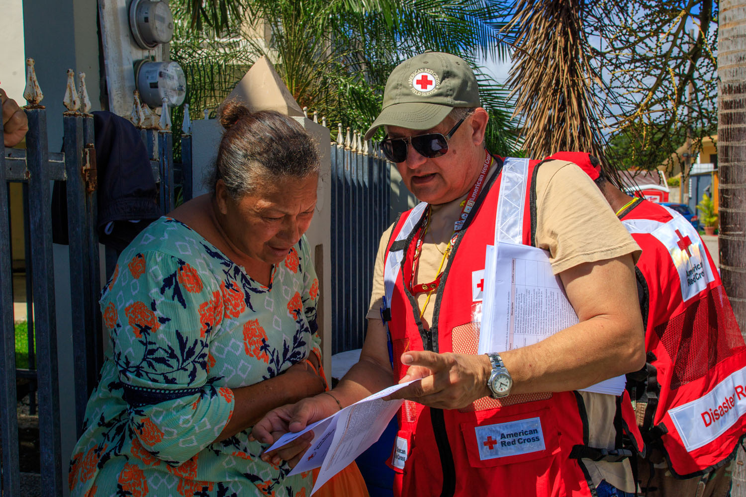 February 1, 2020. Yauco, Puerto Rico. Red Cross team member José, who is from the capital of Puerto Rico, gives Lucila information on how to prepare for future emergencies. Photo by Isaac León/American Red Cross
