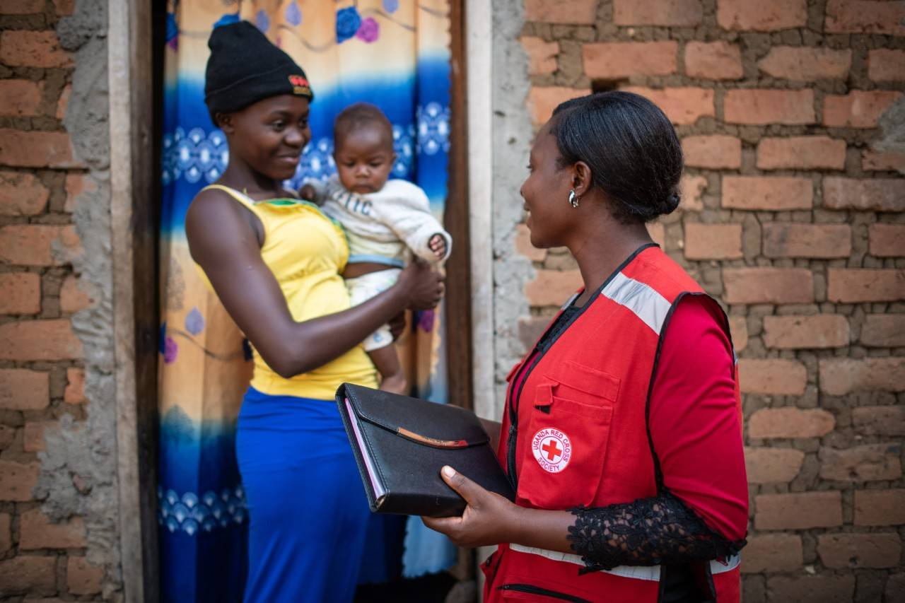red cross worker speaks to lady with baby