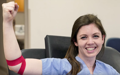 Video screenshot - woman raising her arm after giving blood