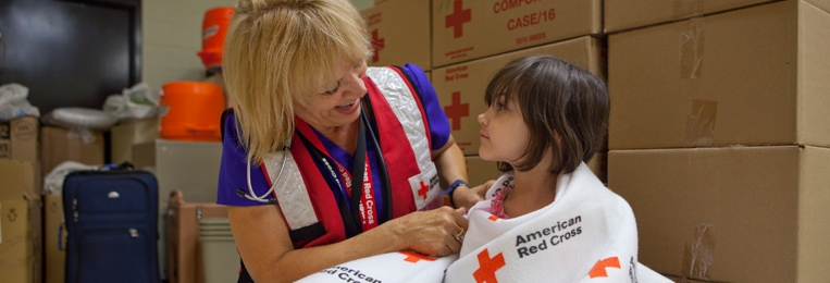Red Cross volunteer comforting little girl in a shelter