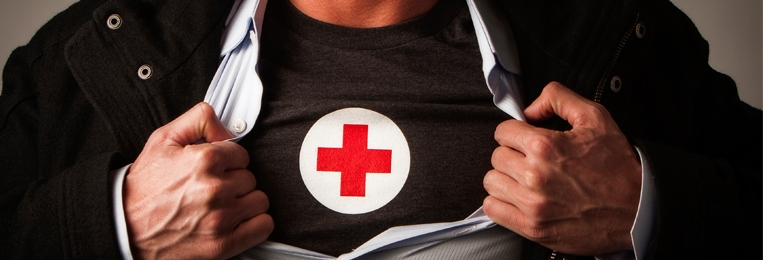 A man in a jacket who is prentending to be a hero by pulling it apart to expose a Red Cross t shirt