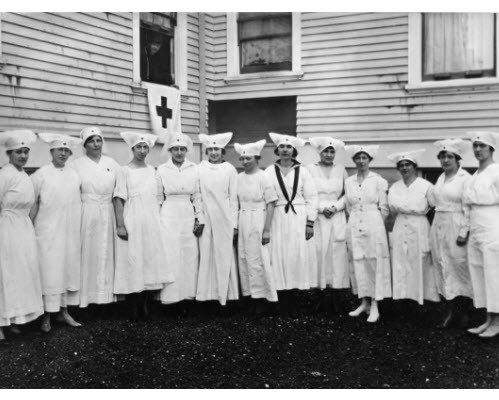 Line of Red Cross nurses dressed in white uniforms