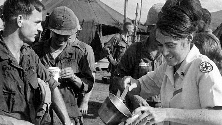 Red Cross nurse pours water for soldiers in Vietnam