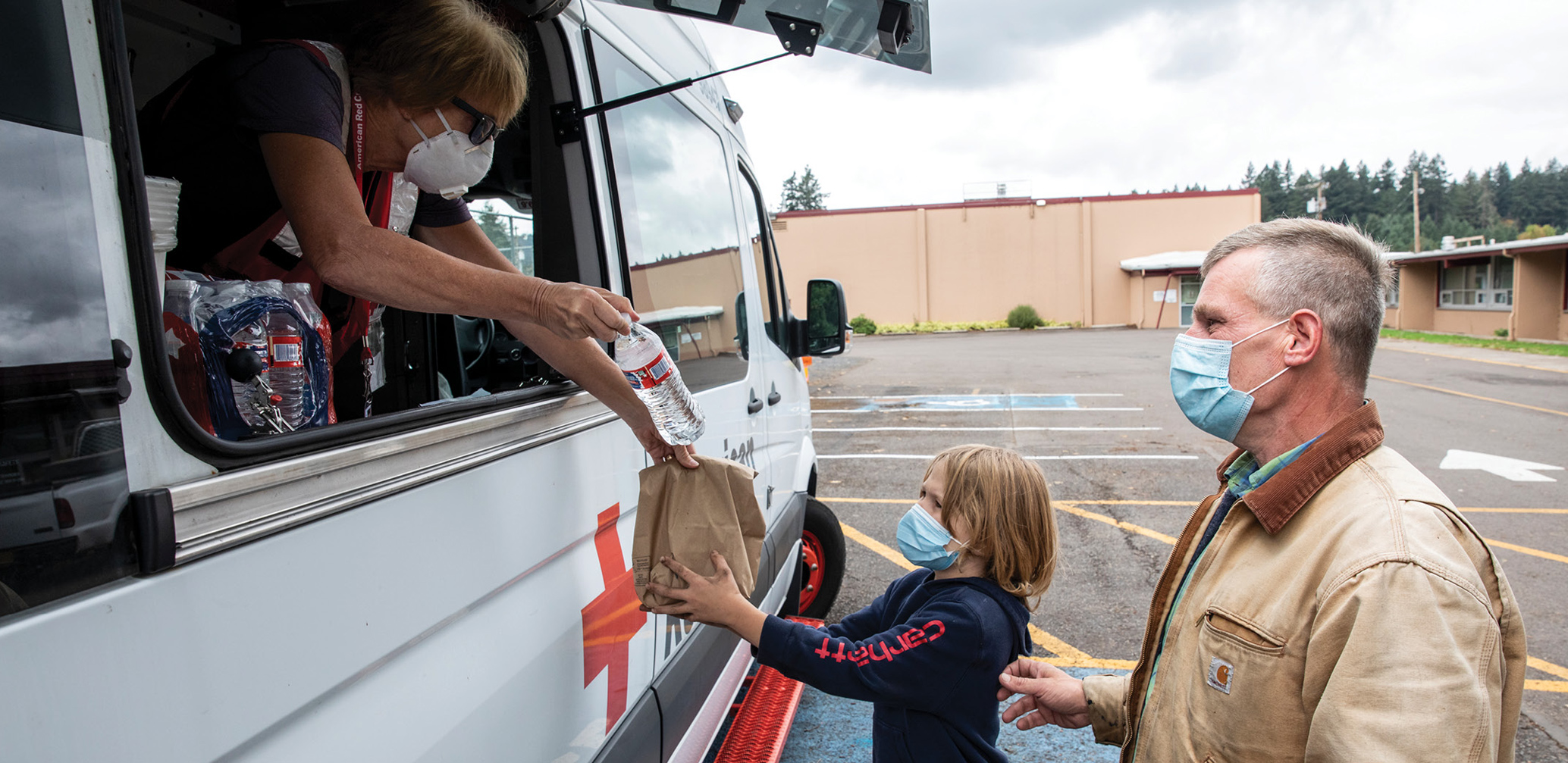 Lyons, Oregon. American Red Cross volunteer Deb McDaniel hands a meal to Jaden,8 years old, and Gary at a supply pick-up location of the American Red Cross