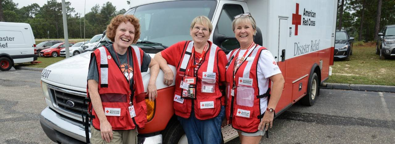 Group of women who are wearing Red Cross vests and standing in front of a Red Cross emergency response vehicle.