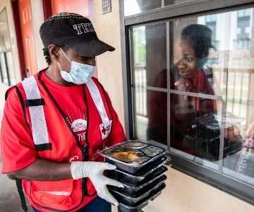 Volunteer in emergency response vehicle hands out meals