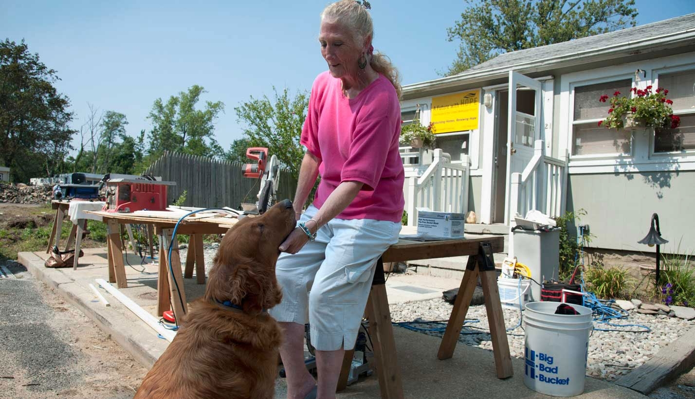 Woman takes a break repairing her home to play with her dog