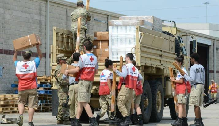 Volunteers and active-duty US Army service members work together to load three convoys of Army high-profile vehicles with supplies.