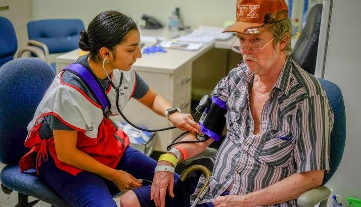 Red Cross Volunteer Nurse Veronica, RN checks the blood pressure of shelter resident Mark