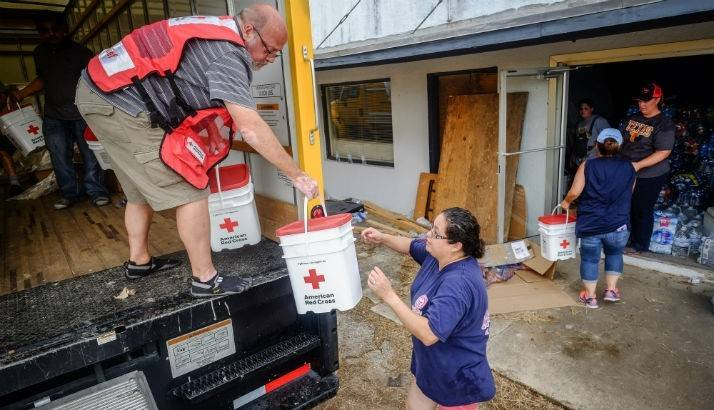 Red Cross volunteer Sam Glick hand off Clean-Up Kits to Jennifer Awardo
