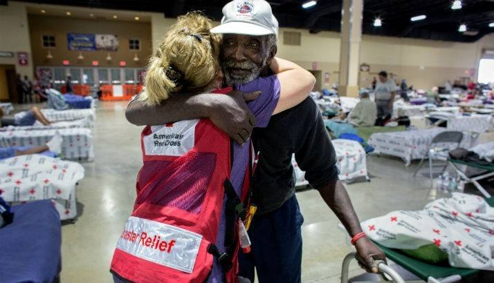 Volunteer hugs man in shelter