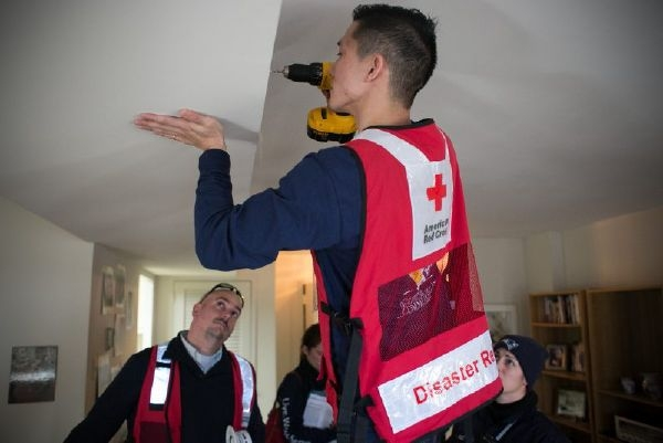 Red Cross volunteer installing a smoke alarm in ceiling of residence.