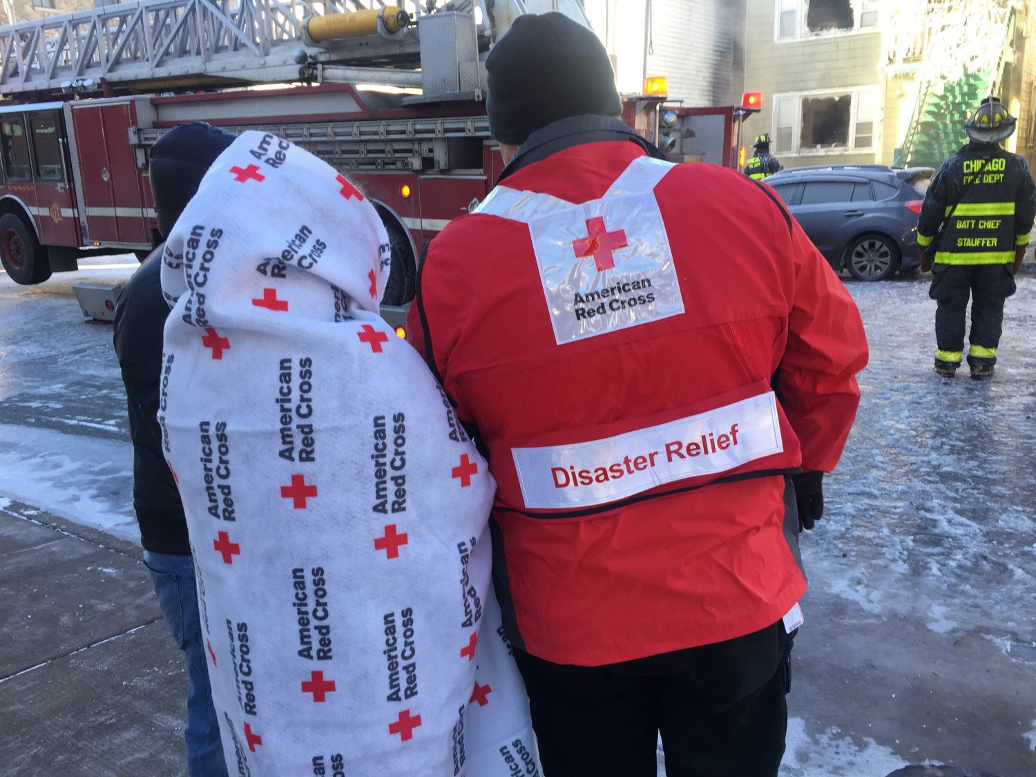 Chicago Red Cross Disaster Relief Volunteer assists victim wrapped in a Red Cross blanket