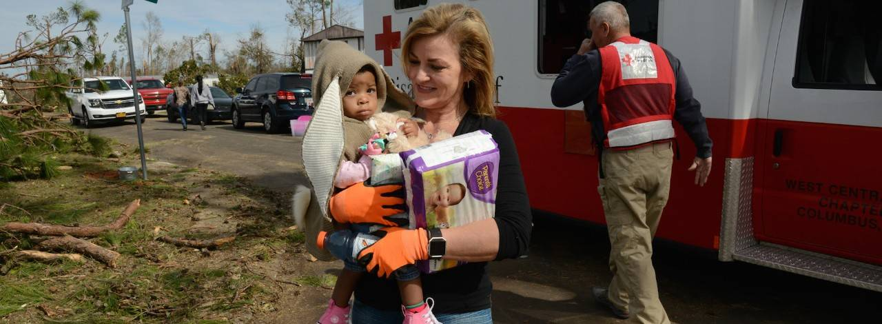 January 28, 2017.  Albany, Georgia. Sixteen-month-old Cayli, held by her neighbor Beverly Presley, receives diapers and snacks from Red Cross volunteer Jennifer Briggs. Photo by Daniel Cima for the American Red Cross
