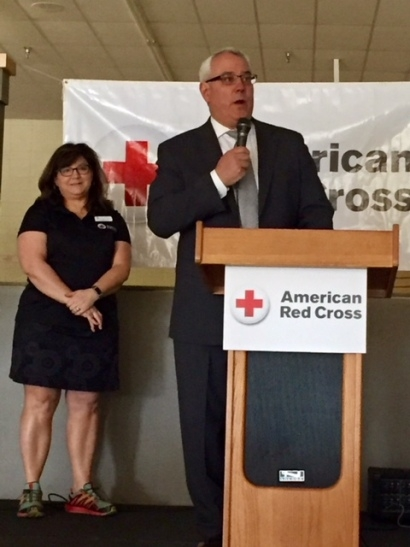 Red Cross staff member standing behind podium speaking into microphone