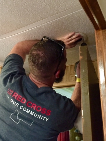 A Red Cross volunteer installs a smoke alarm in the ceiling of a house