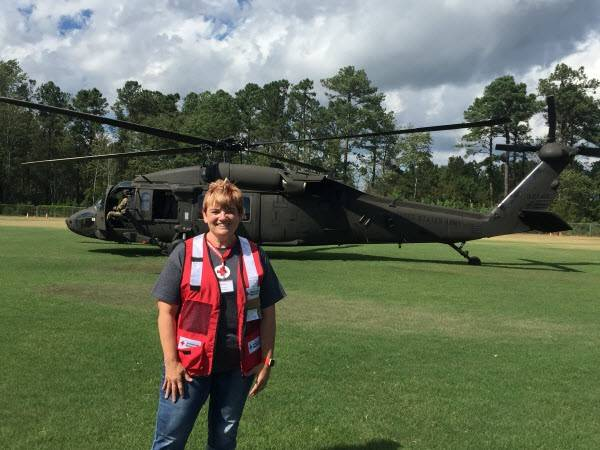 Red Cross volunteer Shellie Creveling stands in front of a National Guard helicopter