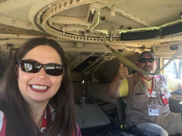 Red Cross volunteer LayLa Johnson rides in military humvees