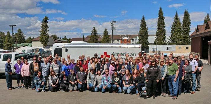 Group of people pose in front of Red Cross emergency response vehicle