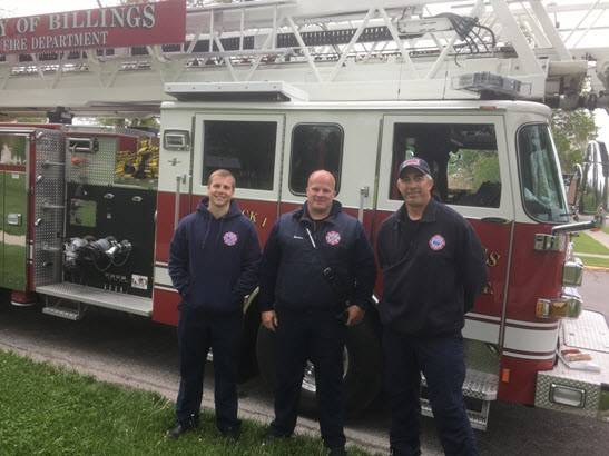 Three firemen in front of fire truck