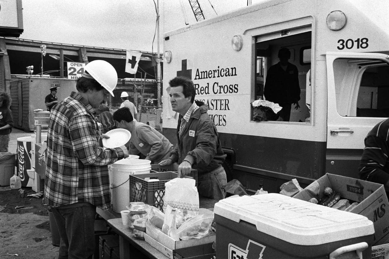 A Red Cross worker provides meals to people near the site of the Cypress Street Viaduct of the Nimitz Freeway Interstate 880 in Oakland, California during the aftermath of the Loma Prieta earthquake.