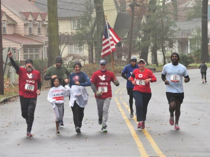 Red Cross New Jersey Runners running down the street with the American Flag.