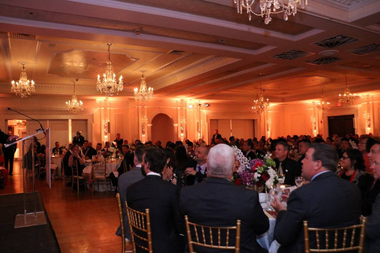A banquet room with people sitting at tables and chairs attending the Long Island Red Cross Heroes Gala