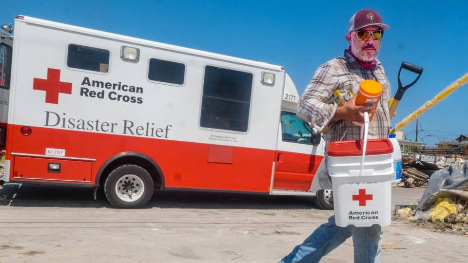 Red Cross volunteer carrying disaster relief supplies across a road.