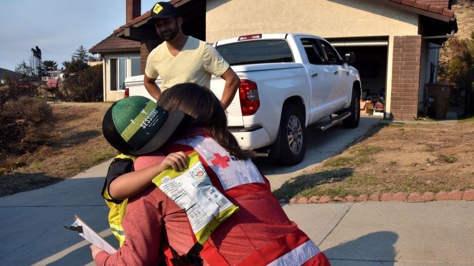 Red Cross volunteer hugging child in front of his father and house.