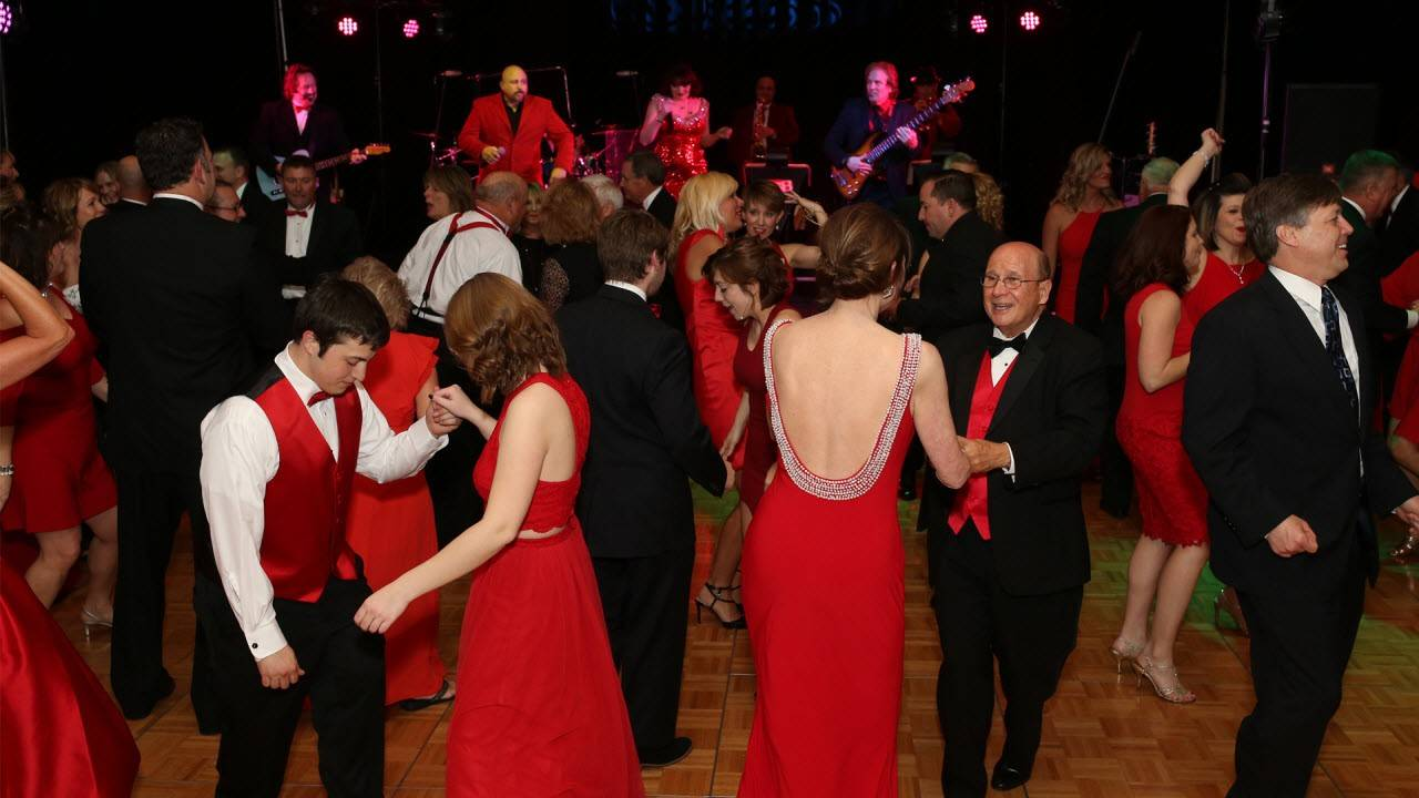 men and women dressed in black and red dancing at the Wrapped in Red Kentucky Red Cross Gala