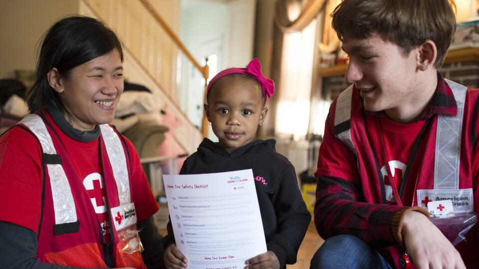 Red Cross volunteers educate child about home fire safety