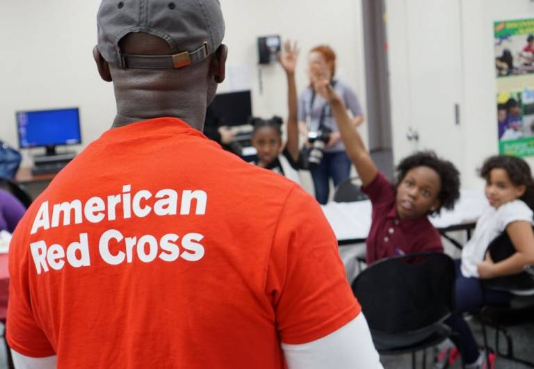 Red Cross instructor stands in front of children
