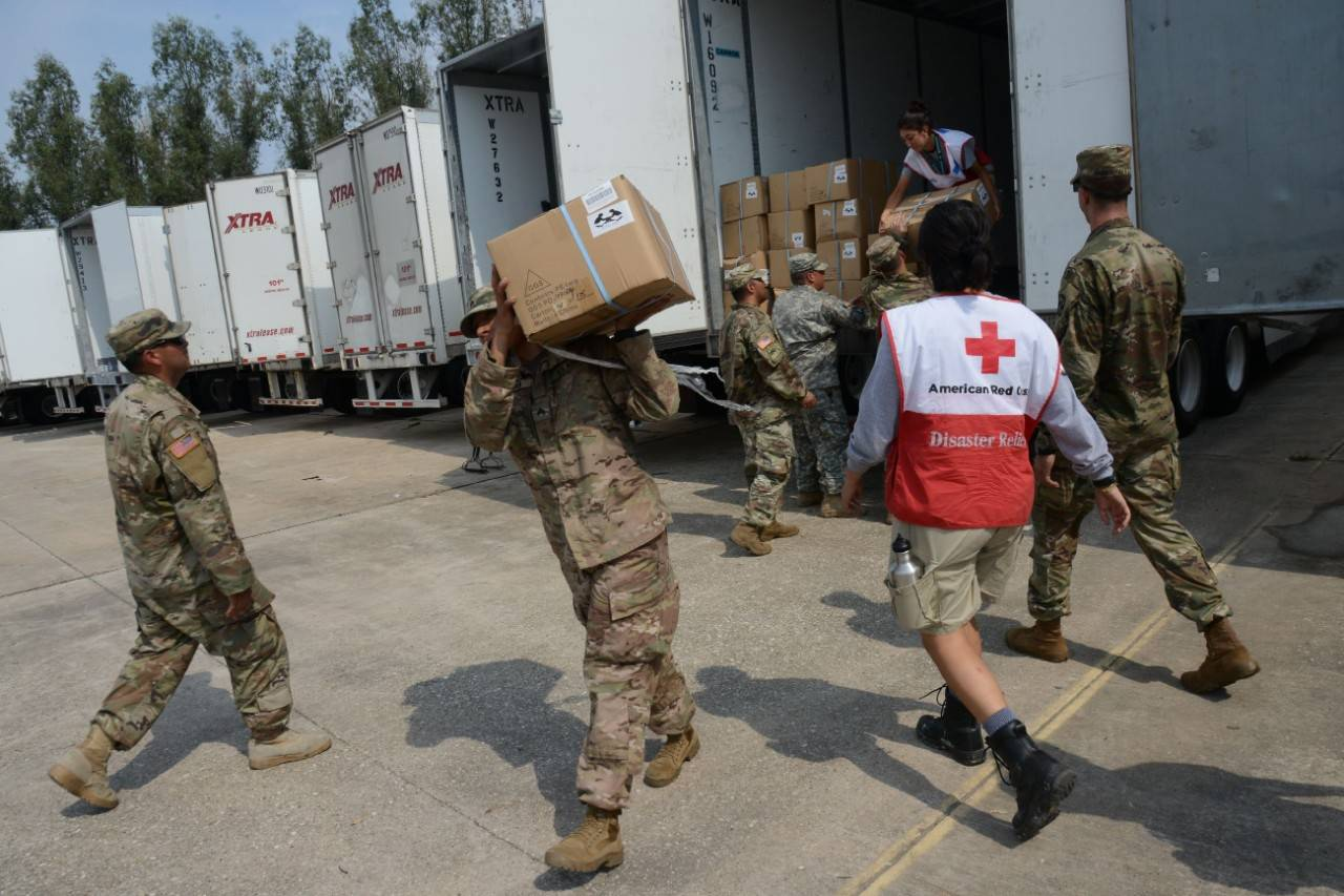 Members of the military help unload a Red Cross supply truck