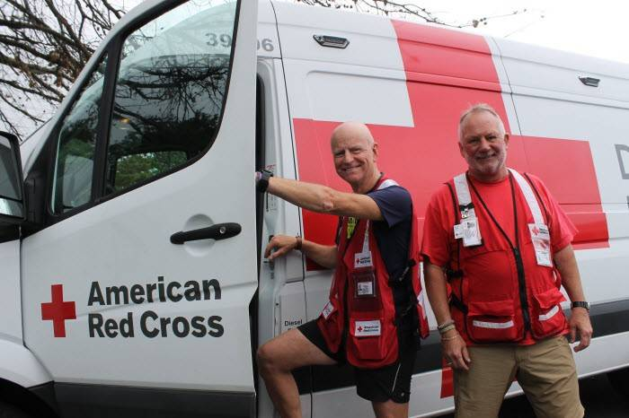 Red Cross volunteers, Federico Materazzi and Bryan Ward getting into an emergency response vehicle.
