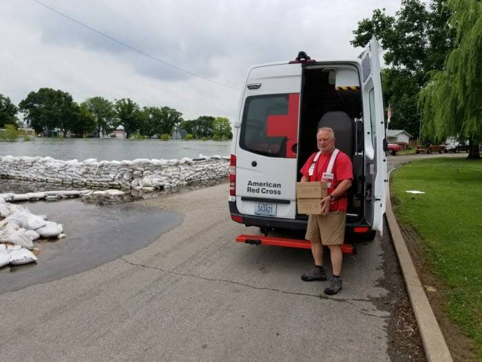 Red Cross volunteer unloading supplies from a Red Cross van delivering supplies to flood victims in Missouri.