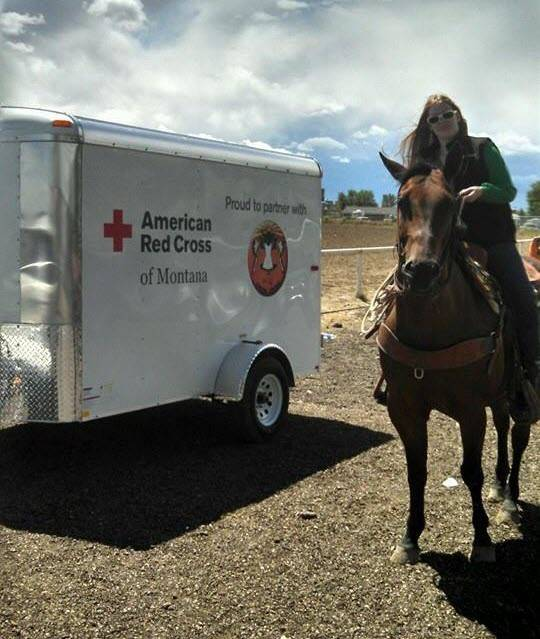 Red Cross female employee on horseback in front of Red Cross trailer.
